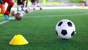 Soccer ball on green artificial turf between cones maker with blurry soccer team training