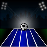 Soccer ball on green background, bright spotlights Stock Images
