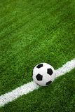 Soccer ball on green field. Close up of soccer ball on white line on green field Stock Images