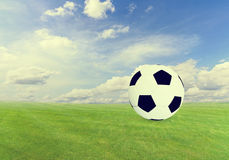 Soccer ball on  green field with blue sky Stock Photography