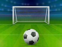 Soccer ball on green field in front of goal post Stock Photos