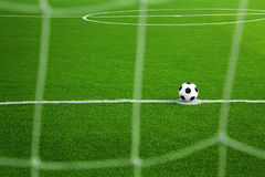 Soccer ball on green field with net foreground. In a stadium Royalty Free Stock Photography