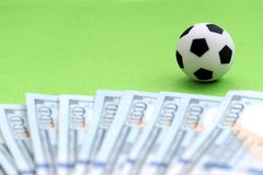 A soccer ball on a green field, next to hundred-dollar bills of the US. Shallow depth of field. Concept money and football, the pr royalty free stock image
