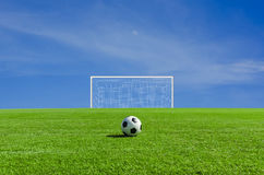 Soccer ball on the green field. With sky stock image