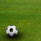 Soccer ball on green football field Stock Photo