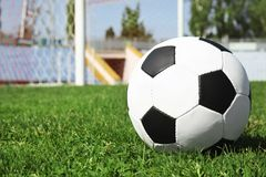 Soccer ball on green football field grass against net. Space for text stock image