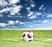 Soccer ball on green grass. And blue sky background Stock Image
