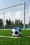 Soccer ball on green grass. In front of goal net stock image