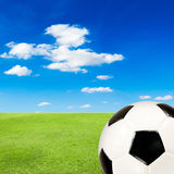 Soccer ball with green grass field against blue sky. Background Royalty Free Stock Image