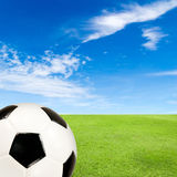Soccer ball with green grass field against blue sky Royalty Free Stock Images