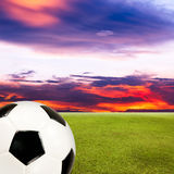 Soccer ball with green grass field against sunset sky Royalty Free Stock Images