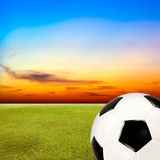 Soccer ball with green grass field against sunset sky. Background Stock Photos