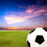 Soccer ball with green grass field against sunset sky Royalty Free Stock Photos