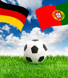 Soccer ball on green grass and flags of germany and portugal Royalty Free Stock Images