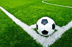 Soccer ball on green grass. Football field in the corner stock photos