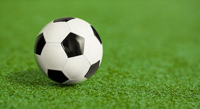 Soccer ball on green grass playground royalty free stock photography