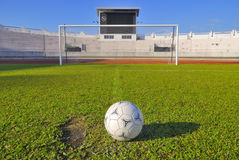 Soccer ball on green grass in stadium. And blue sky royalty free stock photography