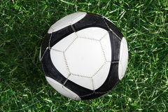 Soccer ball on green grass. Top view stock photography