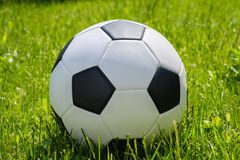 Soccer ball on green grass. Soccer white ball on green grass close up royalty free stock images