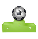 Soccer ball on green pedestal Stock Photo