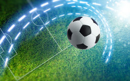 Soccer ball on green soccer stadium. Abstract sports background - soccer ball on green stadium with white layout. Bright spotlight illuminates soccer field Royalty Free Stock Images