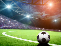 Soccer ball on green stadium, arena in night illuminated Royalty Free Stock Photo