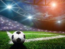 Soccer ball on green stadium, arena in night illuminated Stock Images