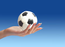 Soccer ball in hand. Hand holding soccer ball over blue sky background Royalty Free Stock Photos