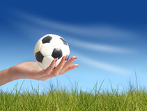 Soccer ball in hand. Hand holding soccer ball over blue sky background Stock Image
