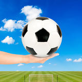 Soccer ball in hand with soccer field and blue sky Stock Images