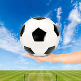Soccer ball in hand with soccer field and blue sky Royalty Free Stock Photo