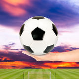 Soccer ball in hand with soccer field and sunset sky Royalty Free Stock Images