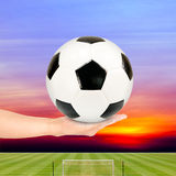 Soccer ball in hand with soccer field and sunset sky Royalty Free Stock Image
