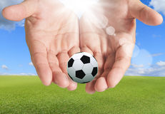 Soccer Ball in hands Stock Images