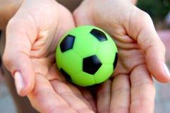 Soccer ball in hands Stock Photos