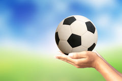 Soccer ball in hands. Blurred natural background Royalty Free Stock Photo