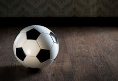 Soccer ball on hardwood floor Royalty Free Stock Images