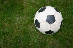 Soccer ball. Hevely used soccer ball. backroad with a green grass Stock Photos