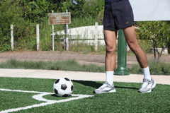 Soccer ball with his feet on the football field Stock Images