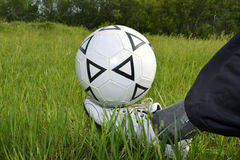 Soccer ball on his leg. Soccer ball on his foot against the grass Stock Photos