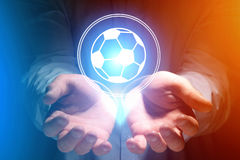 Soccer ball icon over hands - Sport and technology concept. View of a Soccer ball icon over hands - Sport and technology concept royalty free stock image