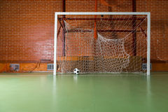 Soccer ball inside empty goal posts. With nets on an indoor court in a red brick building, conceptual with copy space Stock Image