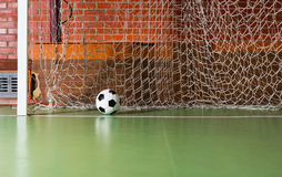 Soccer ball inside the goalposts. Against the back net on an indoor soccer court in a red brick building Royalty Free Stock Image