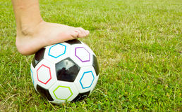 Soccer ball with kids foot on it Royalty Free Stock Photography