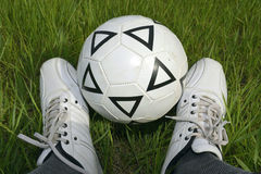 Soccer ball between the legs. Soccer ball between his legs against the grass Stock Images