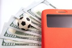 A soccer ball lies on five hundred US dollars next to a mobile phone in a red case. Sports betting concept. Close-up stock photos