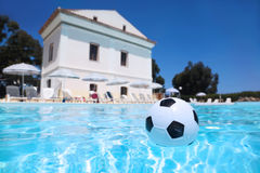 Soccer ball lies in water in pool Stock Photos