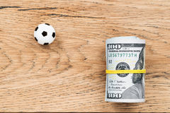 Soccer ball with money on a board Stock Photos