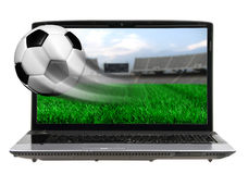 Soccer ball in motion. Flying off laptop screen isolated royalty free stock photography