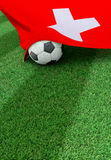 Soccer ball and national flag of Switzerland,  green grass Stock Photography